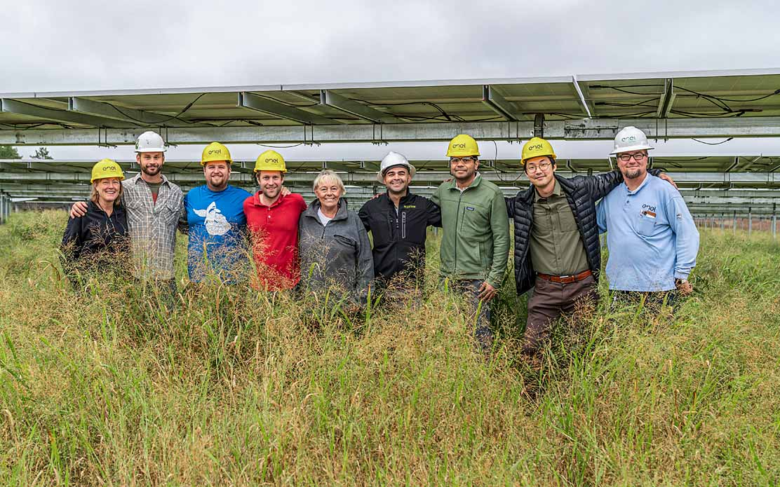 Photo of a group in hard hats standing in a line in tall yellow grass linking arms and posing for a photo in front of a solar panel
