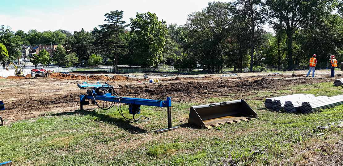 Photo of an open grassy area with equipment from machines scattered around with two individuals standing around wearing safety vests and hard hats. In the distance there is a man driving a tractor through some dirt