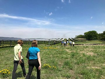 Photo of two women walking side-by-side behind a group of individuals in an open grassy area and rows of solar panels