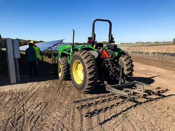 Photo of a large tractor sitting on dirt in front of solar panels while two individuals walk away from the tractor