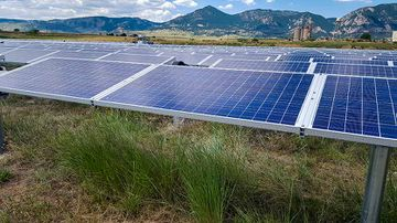 Photo of a row of solar panels in a grassy field with mountains in the background