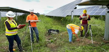 Photo of several individuals wearing safety vests and hard hats standing in between solar panels surveying the land and writing on clipboards