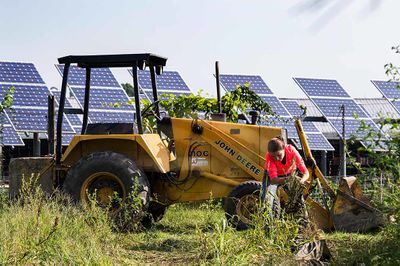 Photo of a woman kneeling in some vegetation in front of a tractor with solar panels in the background
