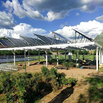 Photo of solar panels arranged on top of a structure surrounded by vegetation and other structures with clouds in the sky