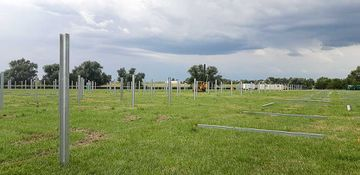 Photo of stormy sky and an open grassy field with cement pillars on the ground organized in rows and standing upright in rows